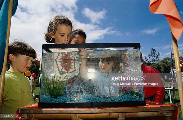 Children Dropping Coins into Tank