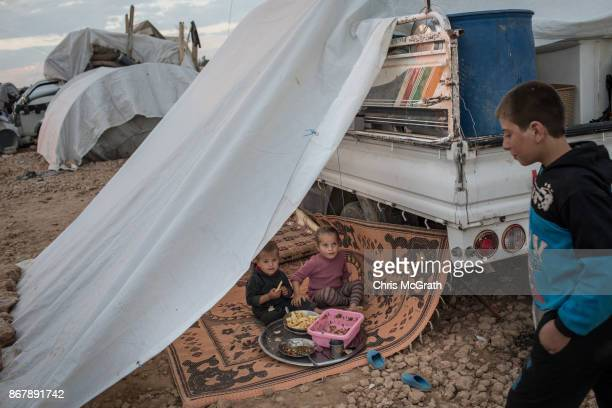 Children eat dinner under a tent attached to the family's truck at a camp for internally displaced people on October 29 2017 in Ain Issa Syria...