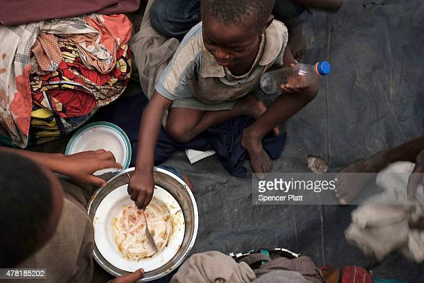 Children eat in a refugee camp for people displaced in conflicts and turmoil that has afflicted Burundi over the last 25 years on June 23, 2015 in...
