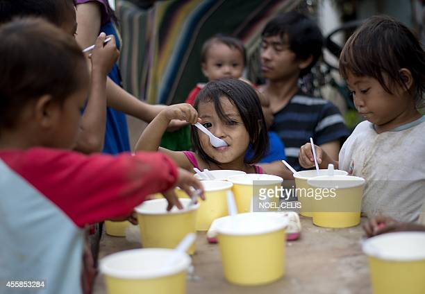 Children eat porridge distributed by the local government at Tumana village in Marikina City suburban Manila on September 21 2014 Thousands of people...