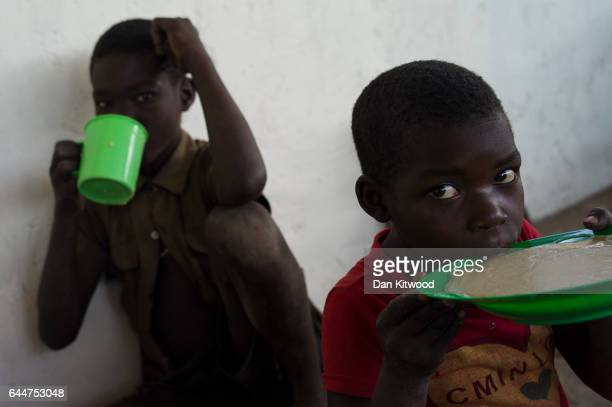 Children eat porridge locally known as Uji as the WFP The 'World Food Programme' distribute hot meals at the Imvepi Settlement on February 23 2017 in...