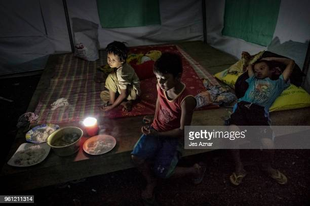 Children eat their last meal of the day before fasting for Ramadan inside their shelter at the Sarimanok tent city on May 15 2018 in Marawi...
