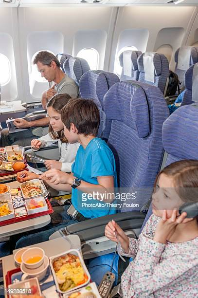 Children eating airline meal on airplane