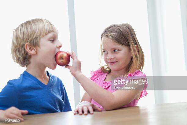 children eating apple in kitchen - altruismo foto e immagini stock