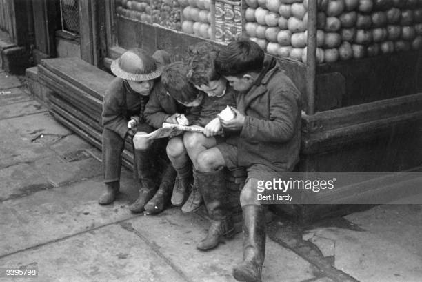Children eating apples as they read a comic outside a shop one little boy is wearing a tinhat Original Publication Picture Post 356 Liverpool unpub