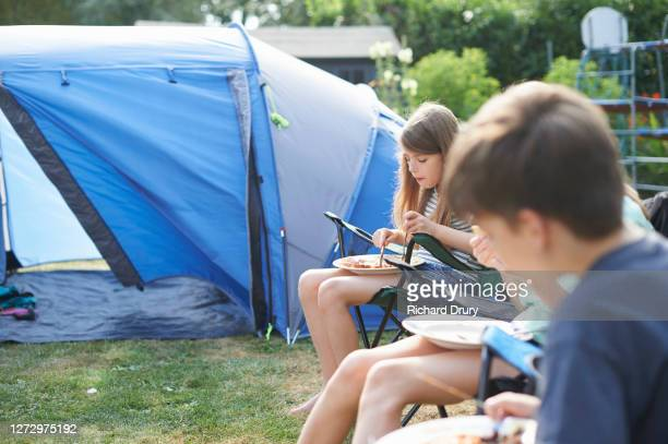 children eating breakfast after camping in their garden - grounds stock pictures, royalty-free photos & images