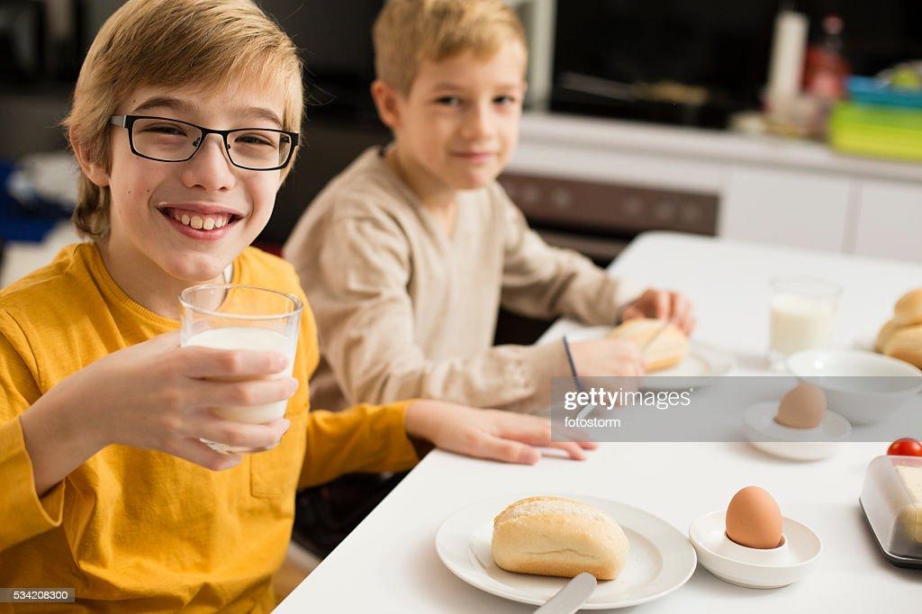 Children eating breakfast, drinking milk in kitchen : Stock Photo