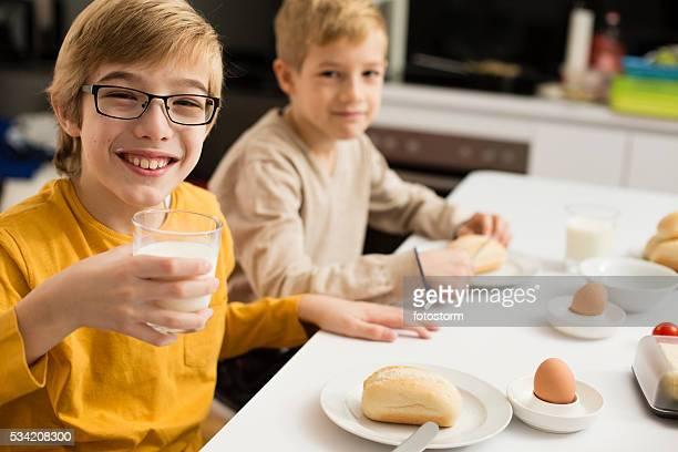 Children eating breakfast, drinking milk in kitchen