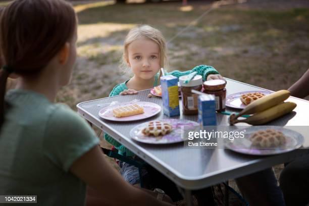 children eating breakfast outdoors on a camping table - kampeertent stockfoto's en -beelden