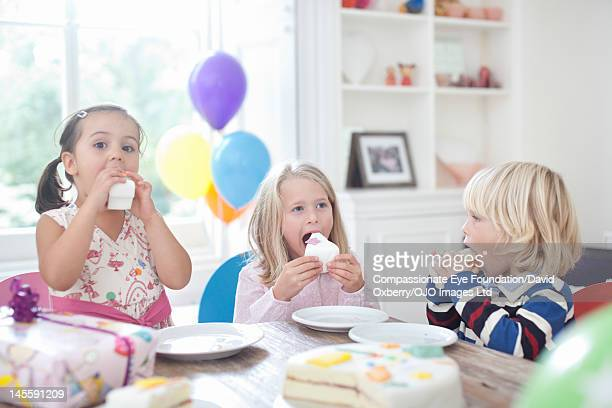 Children eating cake at birthday party