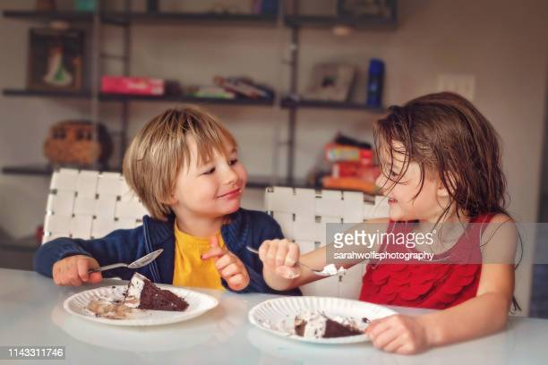 children eating cake together at kitchen table - nur kinder stock-fotos und bilder