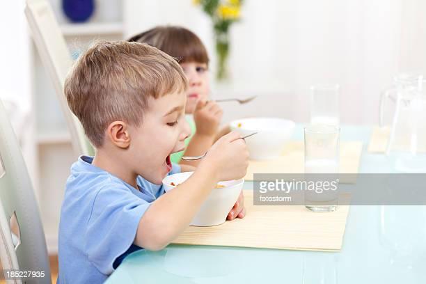 Children eating cereals for breakfast