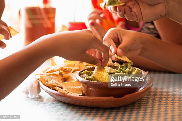 Children eating chips and guacamole