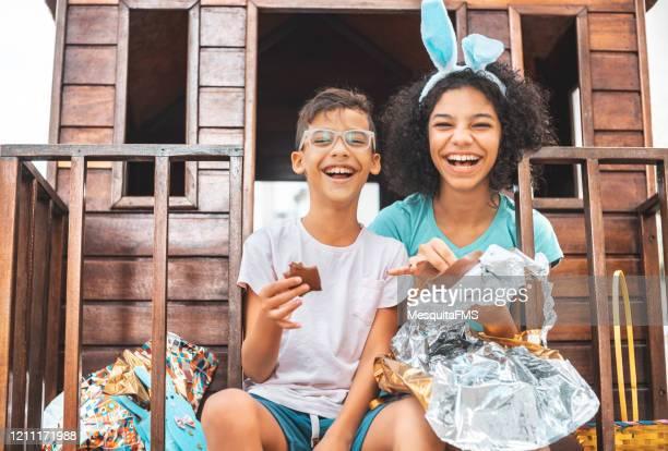 crianças comendo ovo de páscoa de chocolate - easter - fotografias e filmes do acervo