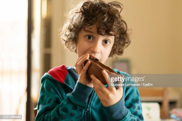 children eating chocolate easter egg - easter egg stock pictures, royalty-free photos & images