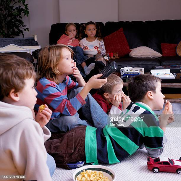 Children eating crisps while watching television