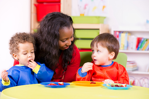 Children eating fruit at a nursery with their carer 140080209