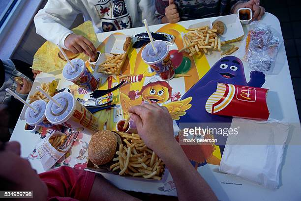 Children eating hamburgers french fries and chicken nuggets from McDonald's