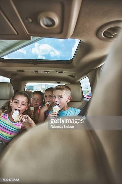 Children eating ice cream cones in the car