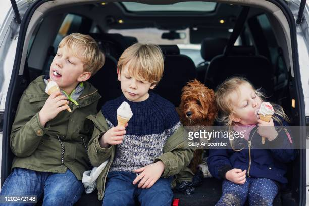 children eating ice cream together in the car - car stock pictures, royalty-free photos & images