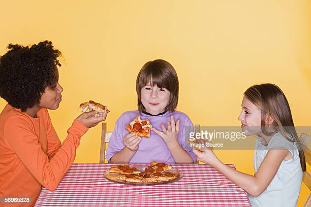Children eating pizza and laughing