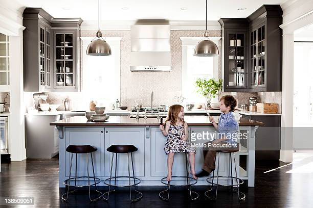Children eating popsicles in kitchen