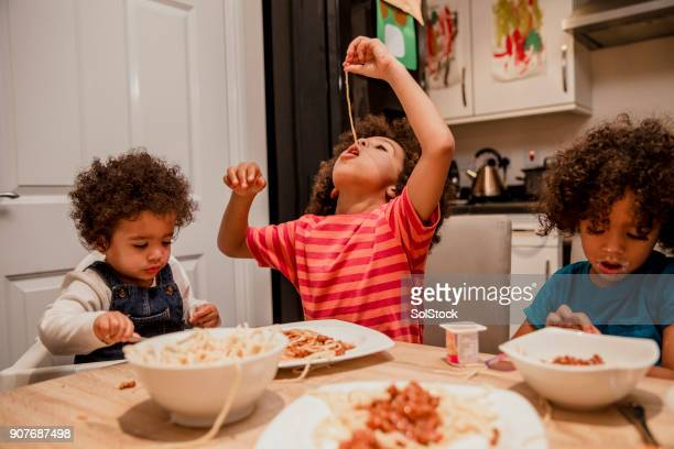 children eating spaghetti and yoghurt - spaghetti stock pictures, royalty-free photos & images