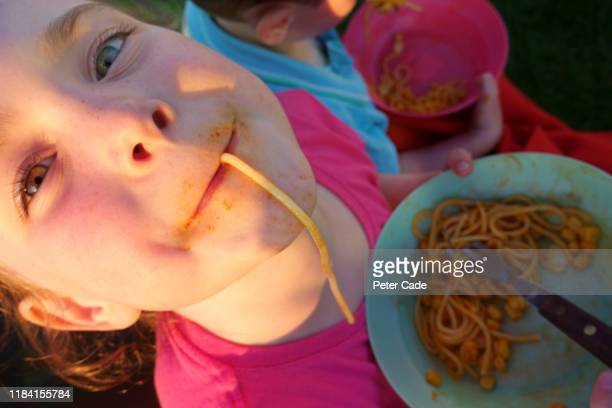 children eating spaghetti outside - british people stock pictures, royalty-free photos & images