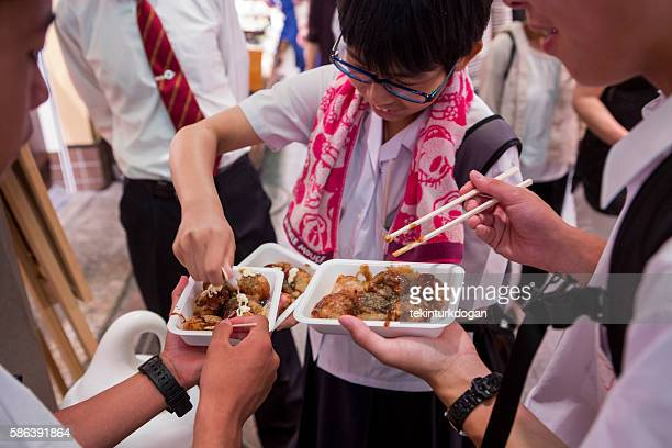 children eating traditional japanese fastfood at nishiki market  kyoto japan - nishiki market stock photos and pictures