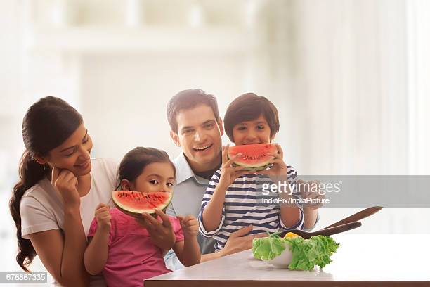 Children eating watermelon slice with their parents at kitchen table