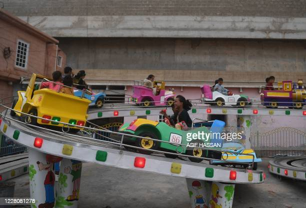Children enjoy a fun fair ride at a playland in Karachi on August 17 after the government announced most of the country's remaining coronavirus...