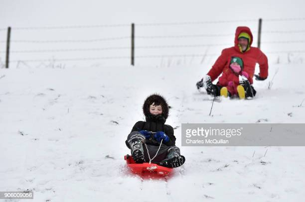 Children enjoy heavy snowfall on their sleds on January 17 2018 in Belfast Northern Ireland The Met Office has placed an amber weather warning alert...