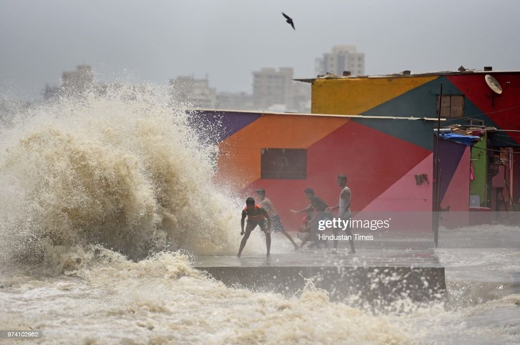 Children enjoy high tide at slum of Bandstand, Bandra, on June 13, 2018 in Mumbai, India.