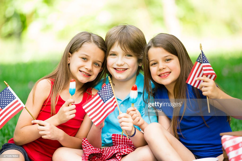 Children enjoy July 4th picnic in summer. American flags, popsicles. : Stock Photo