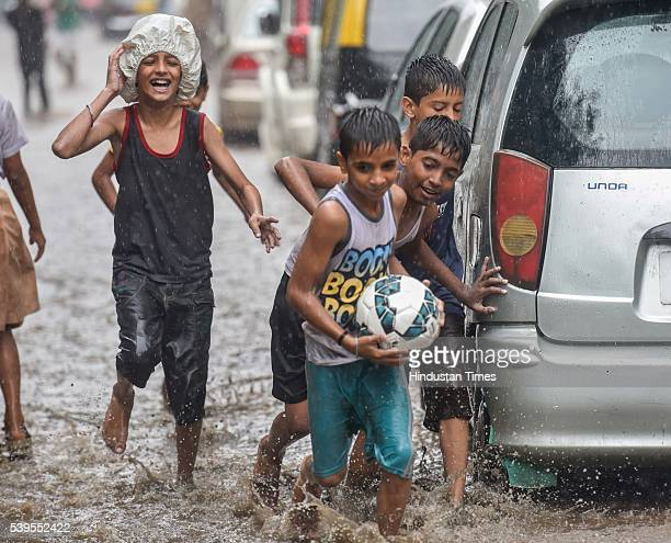 Children enjoy on a flooded street during premonsoon showers on June 11 2016 in Mumbai India Mumbai rains have finally commenced on Saturday morning...