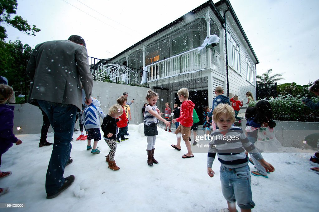 Children enjoy the ice and the snow machine outside a house on Franklin Road in Ponsonby on December 1, 2015 in Auckland, New Zealand. It is the 22nd year Franklin Road residents have decorated their houses with lights for the Christmas season.