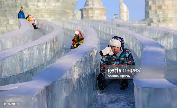 Children enjoy the ice slides during the 33rd Harbin International Ice and Snow Festival at Harbin Ice And Snow World in Harbin China on January 16...