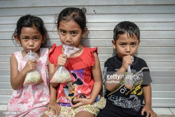 Children enjoy the local drink in a village near Ubud Ubud District Bali Indonesia in November 2018