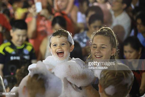 Children enjoy themselves in an avalanche of artificial snow made of foam at Tanglin Mall shopping centre on December 24 2014 in Singapore The mall...