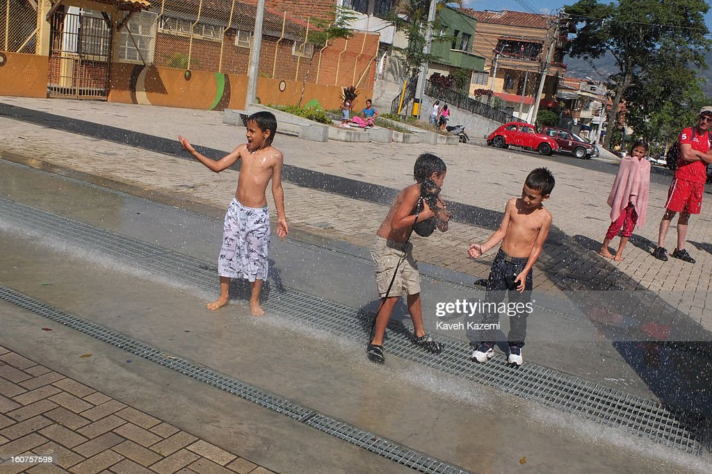 Children enjoy time showering themselves with water coming from pipes installed overhead in the playgrounds built by city's municipality in the Comuna 13 slums on January 5, 2013 in Medellin, Colombia. Comuna 13 is the most notorious slums of Medellin with violence occurring everyday. The slums of Medellin have gone through urban and educational projects to improve the quality of life for its residents.