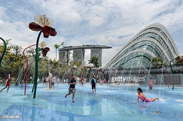 Children enjoy water fountain playground at Garden by the Bay in Singapore on March 19 2014 The programmable water display is linked to sensors which...