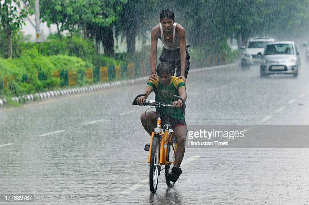 Children enjoying during the heavy rainfall on August 25, 2013 in Noida, India. Many parts of Delhi/Noida experienced heavy rains in the afternoon...