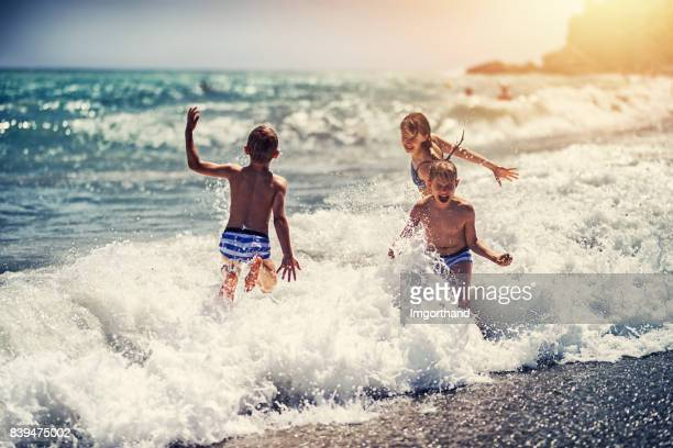 Children enjoying huge waves on beach