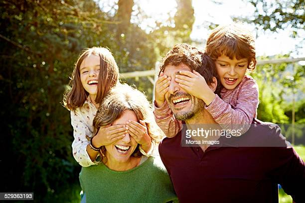 children enjoying piggyback ride on parents - family with two children stock photos and pictures