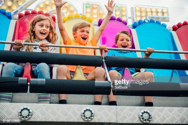 children enjoying the thrill of the rides - amusement park stock pictures, royalty-free photos & images