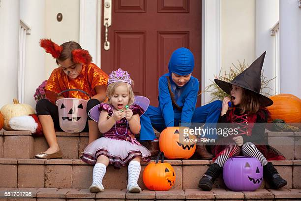 children enjoying treats on steps - halloween kids stock photos and pictures