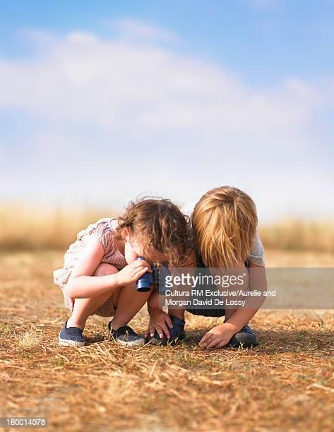 Children examining grassy field