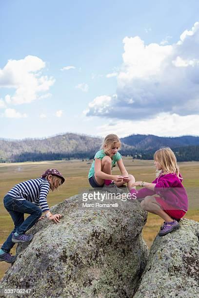 Children exploring rock formations in remote landscape