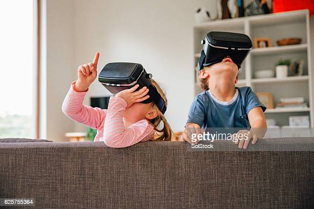children exploring virtual reality technology - simulatore di realtà virtuale foto e immagini stock