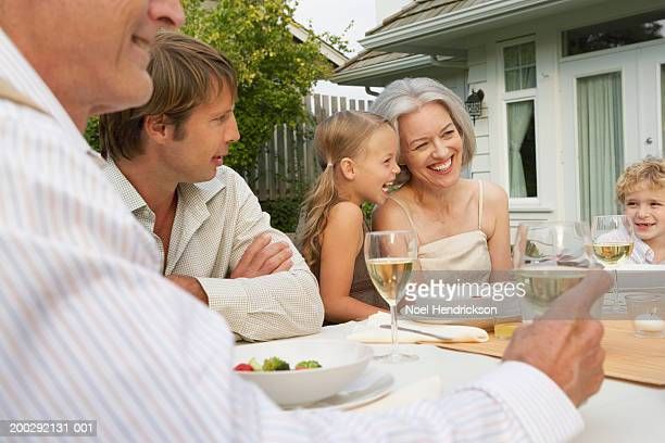 Children (5-7 years), father and grandparents dining on patio, smiling